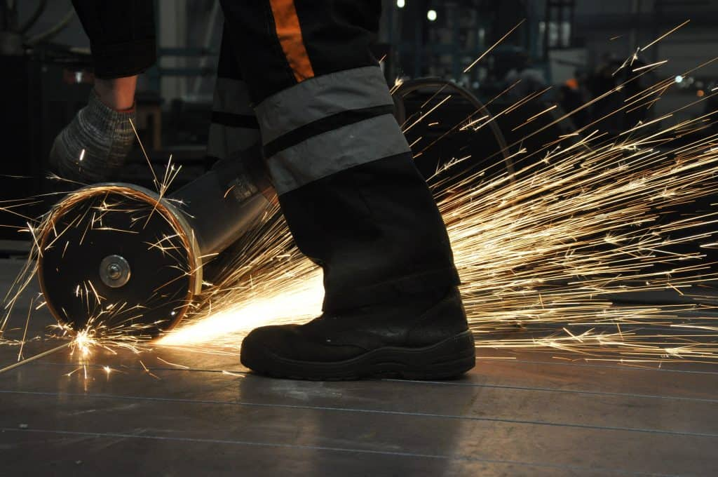 Worker at the factory cuts metal. sparks fly